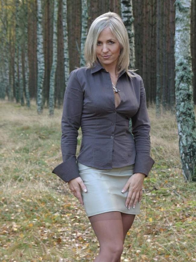 Зрелая в короткой светлой юбке кофточка слегка расстёгнута стоит в лесу