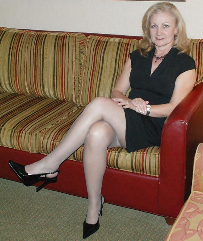 Красивая зрелая женщина лет 45 сидит на диване ножки показывает