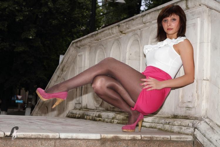 Полу присела на одной ноге в капроне розовой короткой юбке