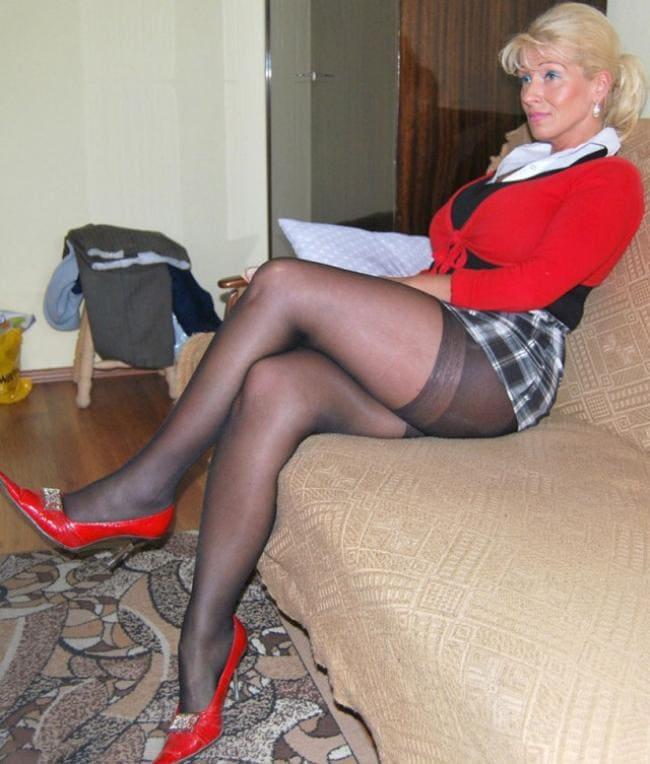 Зрелая мамка сидит в колготках на диване в красных туфлях