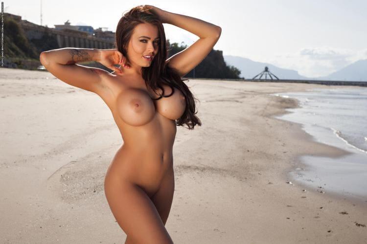 Голая брюнетка с длинным волосом стоит на берегу, показывая свои большие сиськи