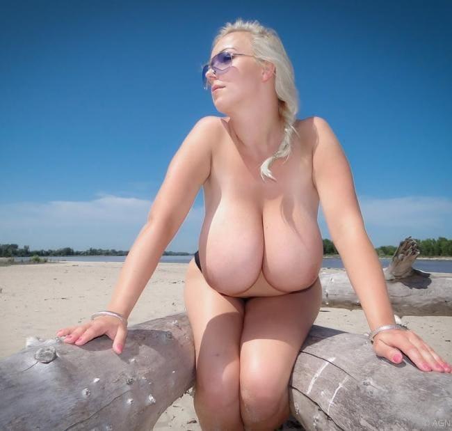 Блондинка голая с большой грудью сидит на бревне