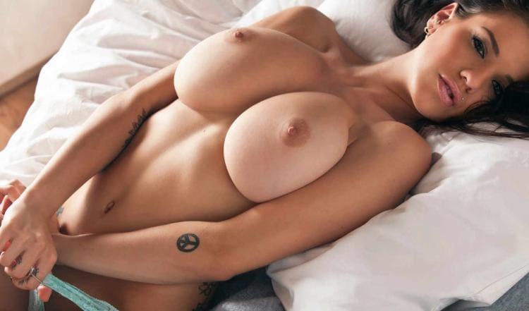 Лежит голая на кровати стягивает трусики