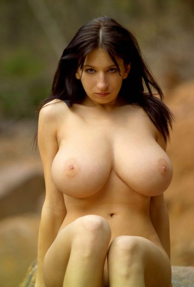 Брюнетка голая с большой натуральной грудью сидит на песке