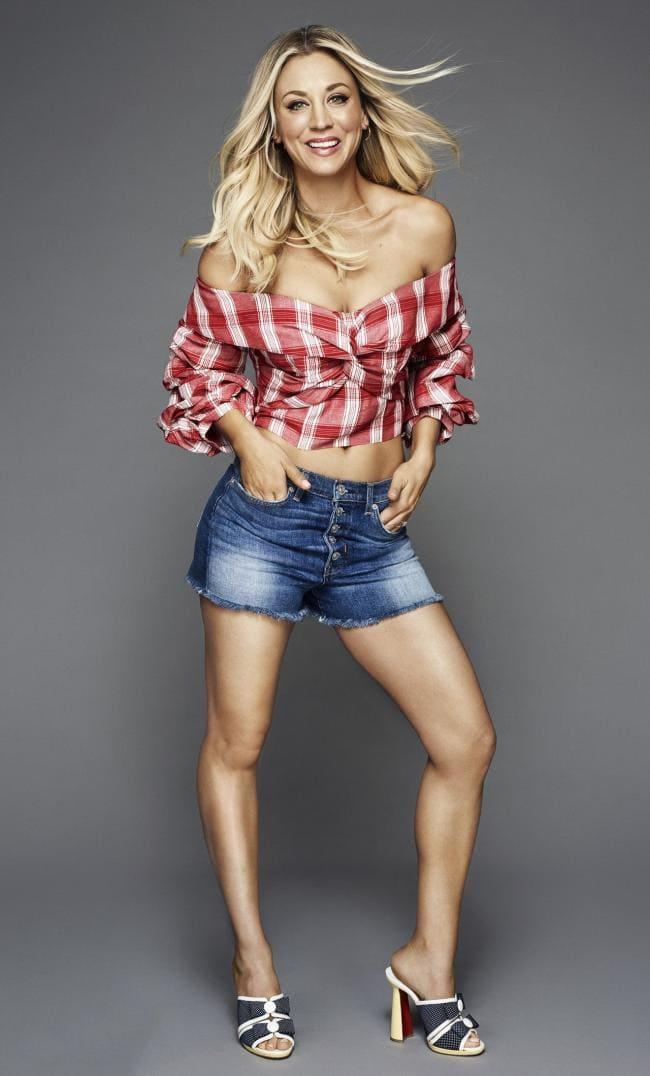 Клетчатая рубашка приспущены рукава, короткие джинсовые шорты, босоножки на высоком каблуке, руки в карманах