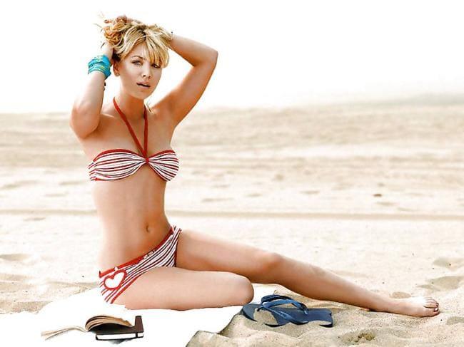 Сидит на песке в купальнике руки подняты на голову
