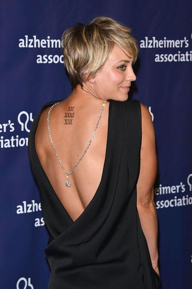 Фото Кейли Куоко с короткой прической стоит задом в платье с открытой спиной видны татуировки