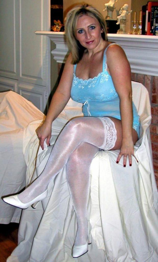 Зрелые блондинки в белых чулках. Сидит на стуле, декольте, большие сиськи, туфли на высоком каблуке,левую ногу положила на правую.