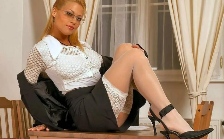 Зрелые блондинки в чулках красиво сидит на столе в белых чулках в деловом костюме, из под высоко задранной юбки видны кружева чулок, на глазах надеты очки, на ногах черные туфли на высоком каблуке.