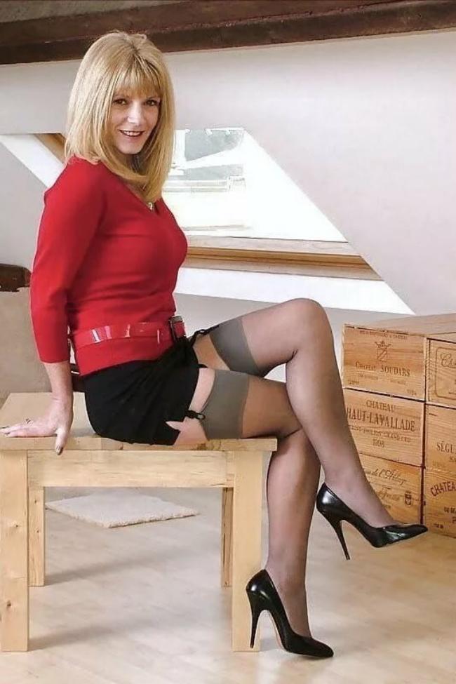 В красной кофте,короткой черной юбке,чулки на поясе, туфли на высоком каблуке