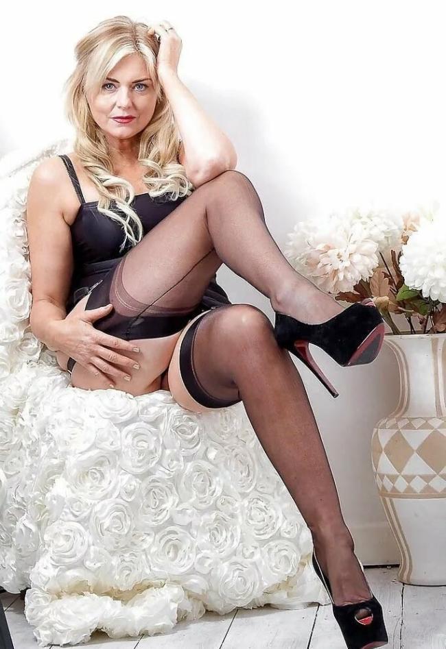 Красивая зрелая блондинка в чулках с длинными волосами сидит в кресле в черных чулках, туфли на высоком каблуке вид снизу
