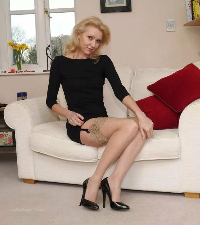 Зрелые блондинки в чулках. Сидит на диване в коротком платье, бежевые чулки на черном поясе, туфли на каблуке
