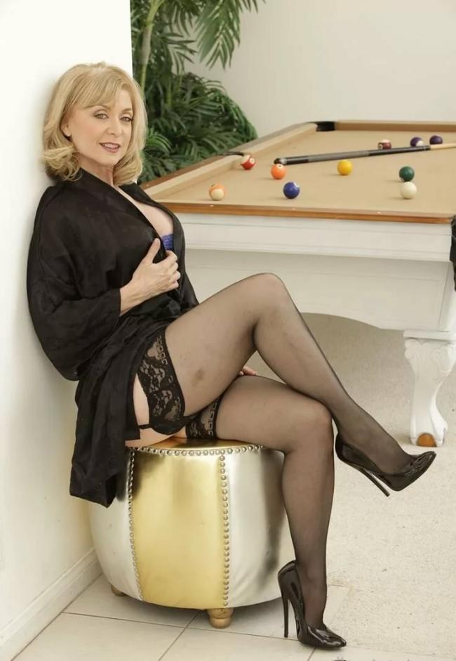Зрелые блондинки в чулках сидит на пуфике возле бильярдного стола, полуголая в чулках и туфлях
