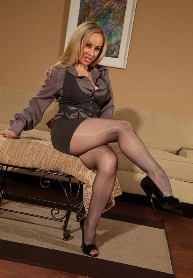 Зрелые блондинки в чулках, такая развратная дама в блестящих колготках сидит на столе накрытом покрывалом., развратно подняла ногу в туфле на высоком каблуке, рот слегка приоткрыт, призывая к сексу.