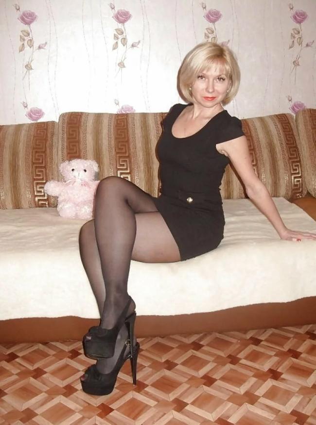 Сидит на диване в коротком черном платье, колготках, высокий каблук
