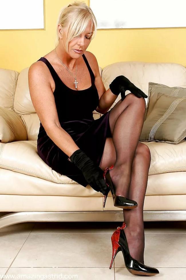 Женщина за 50 сидит на диване в черном платье, плечи оголены, чулочки, туфли на высоком каблуке, перчвтки