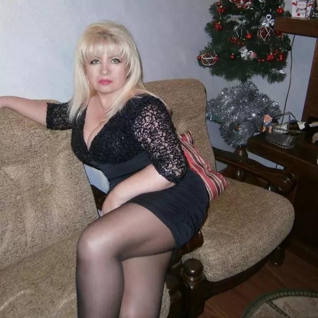 Сидит на диване вполоборота пышная дама в короткой юбке в черных прозрачных колготках