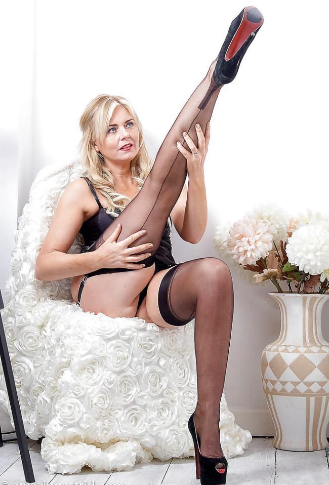 Красивая зрелая блондинка в чулках черного цвета и на каблуках сидит в кресле, одну ногу подняла кверху