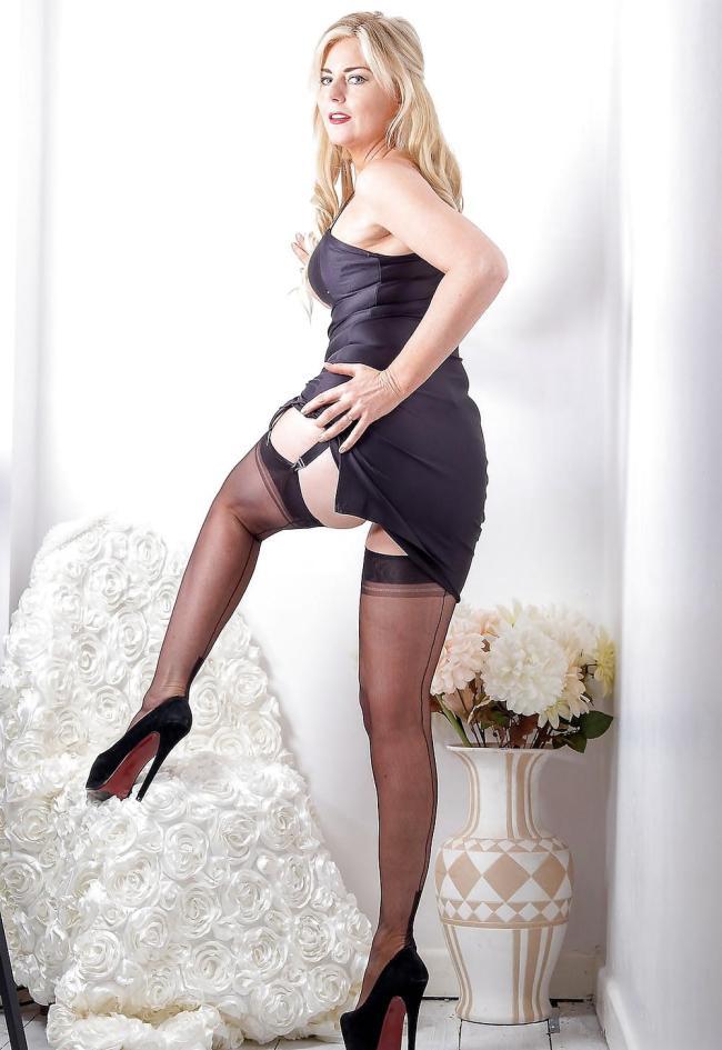 Шикарная зрелая в черном пеньюаре стоит развернувшись вполоборота, ногу поставила на кремсло