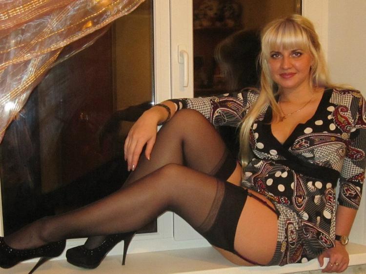 Зрелые блондинки в чулках телка сидит на подоконнике ,туфли черные на каблуке, взгляд похотливый видно, что она готова к сексу.