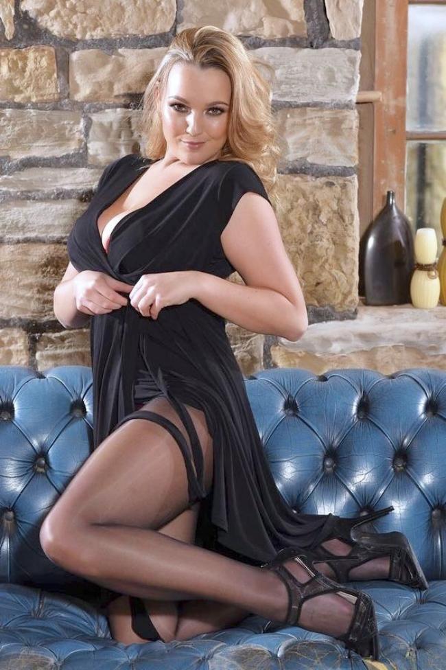 Зрелые блондинки в чулках и в черном платье стоит на коленях на диване в туфлях на каблуке, развязывая платье, смотрит похотливо.