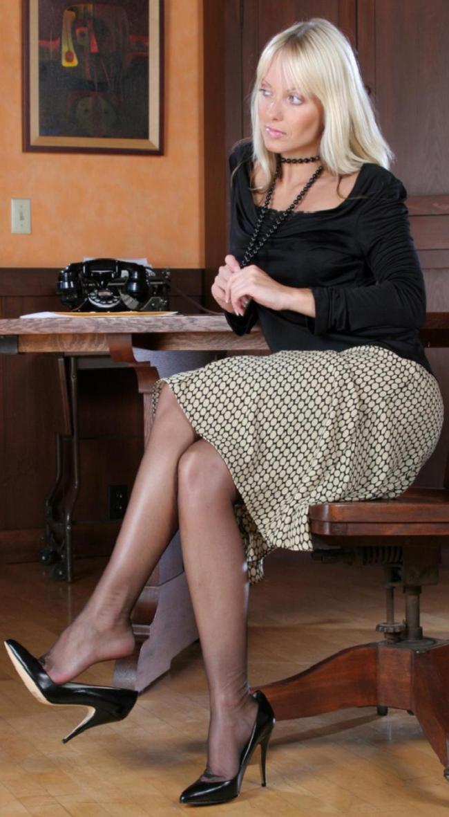 Зрелые блондинки в чулках скромно сидит на стуле немного приспустила туфлю и кокетливо смотрит в сторону от объектива. На стене висит картина, на столе на который она опирается локтем левой руки стоит черный дисковый телефон.