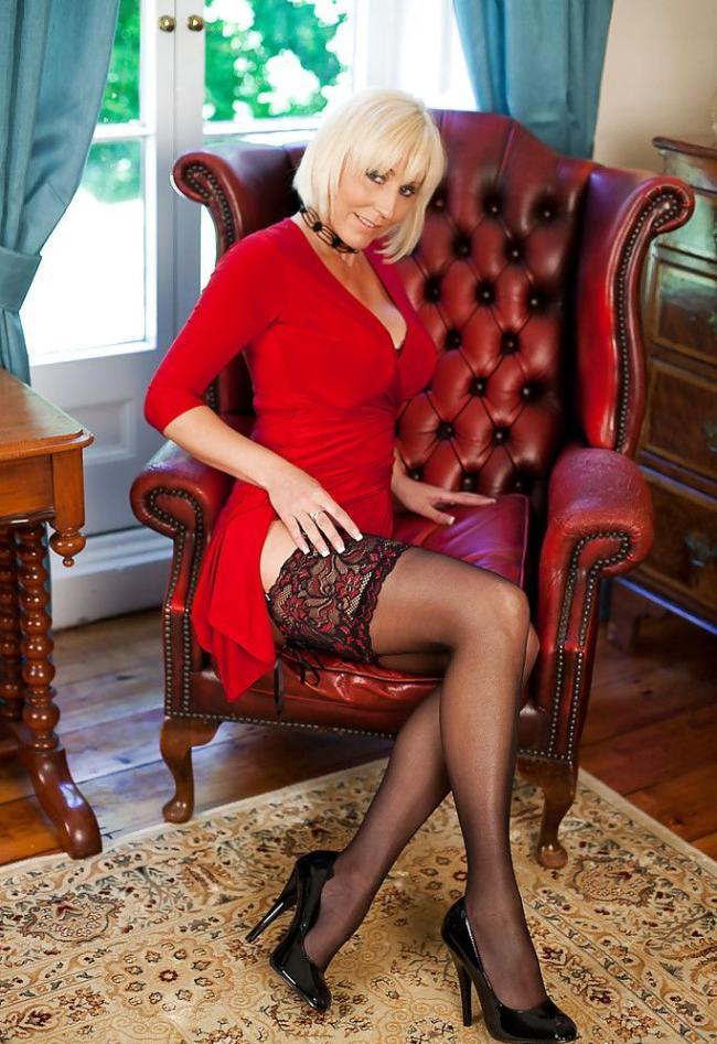 Зрелые блондинки в чулках. Сидит в красном кожаном кресле в красном платье в чулках и туфлях на высоком каблуке. На заднем плане двери со стеклами через которые видна зелень на улице.