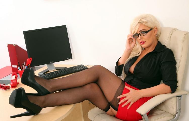 Сидит в кресле , сексуальные очки, ноги на столев черных чулках, туфли на высоком каблуке