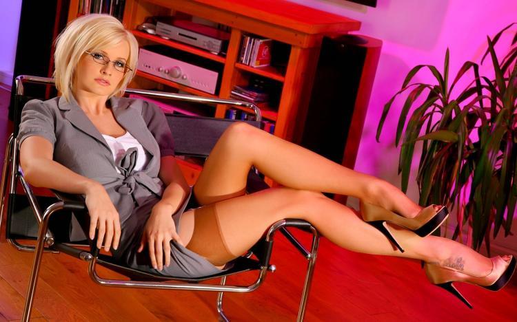 Зрелые блондинки в чулках. Блондинка в очках, сидит в кресле вытянула ножки в коричневых чулках на поясе туфли на каблуке, хорошо виден подъем