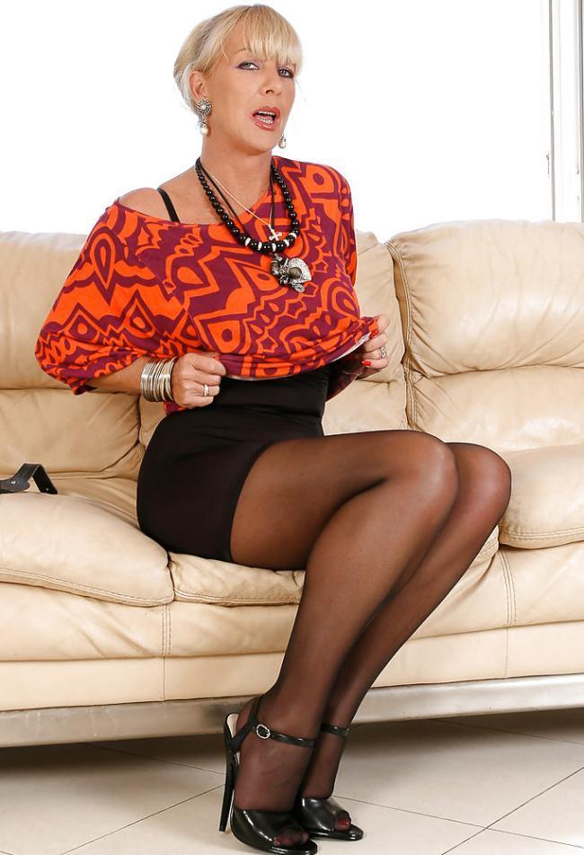 Зрелые блондинки в чулках сидит на диване в колготках поднимает юбочку, приоткрыла ротик
