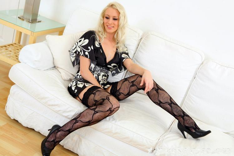 Зрелые блондинки в чулках чулки на поясе с рисунком, сидит на белом кожаном диване немного раздвинув ноги в туфлях на высоком каблуке.