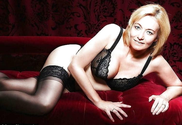 Зрелая в черном бюстике черных чулках лежит на красном диване