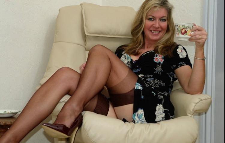 Зрелые блондинки в чулках женщина сидит в кресле вид снизу платье бесстыдно задрала, взгляд блядский в левой руке держит чашку.