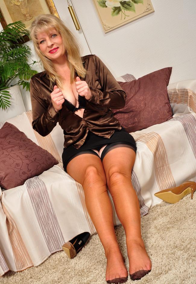 Зрелые блондинки в чулках женщина сидит на диване туфли сбросила, расстегнула кофточку показывая глубокое декольте