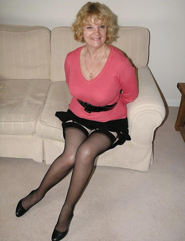 Зрелая за 50 лет с большой грудью в черных чулках на поясе сидит на диване, короткую юбку задрала, улыбается