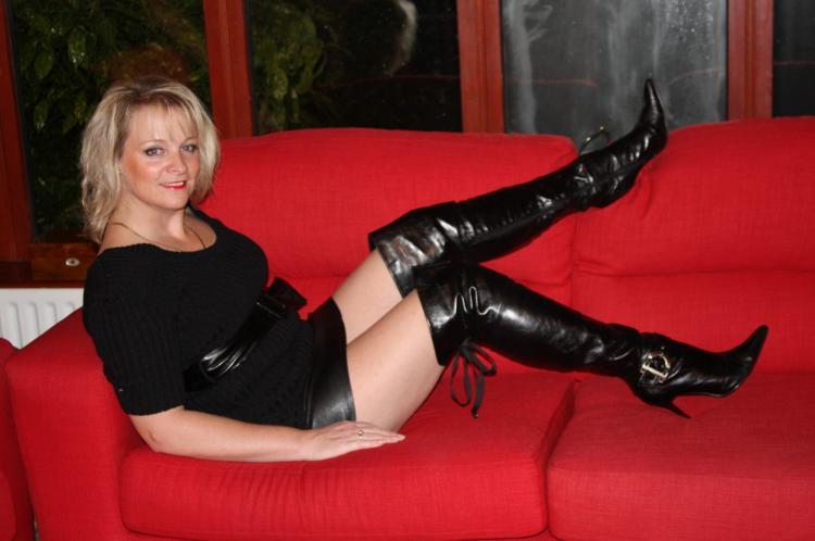 Зрелая блондинка полулежа на красном диване в черных ботфортах