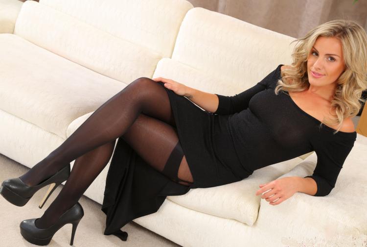 Красотка в черном платье с большим разрезом в чулках и туфлях на высоком каблуке сидит облокотившись на белом диване