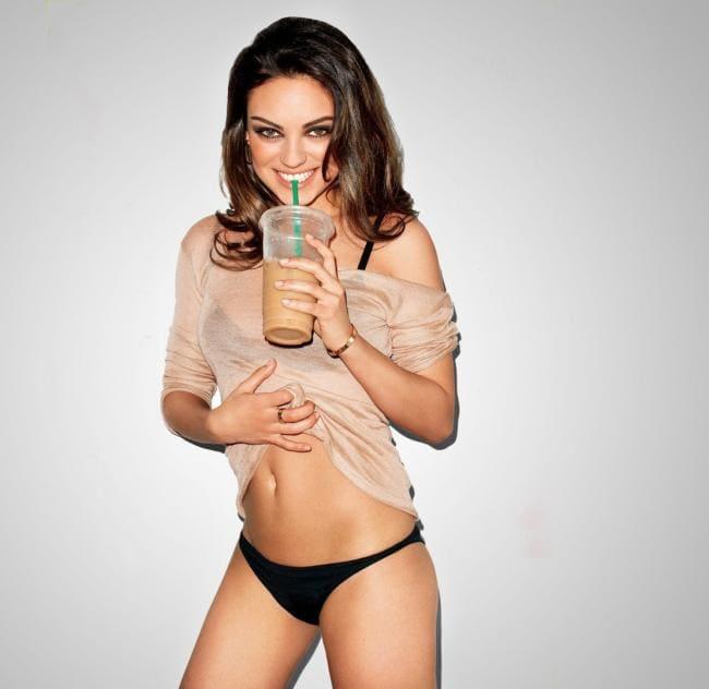 Мила Кунис стоит пьет с трубочки напиток, в трусах, задирает рубашечку оголяя живот