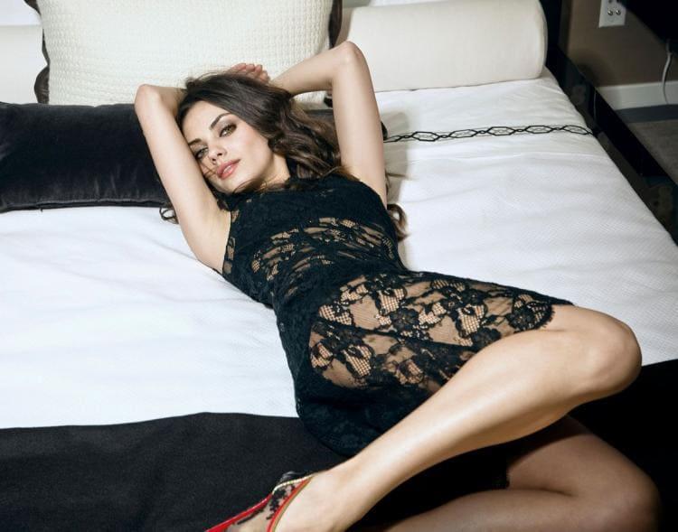Мила Кунис в гипюровом платье лежит на кровати подняв руки показывая подмышки