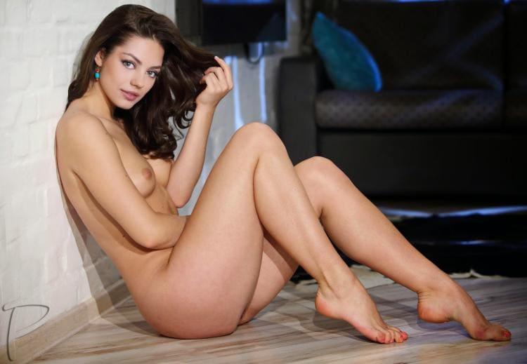 Голая сидит у стены, вид сбоку, ноги стопы