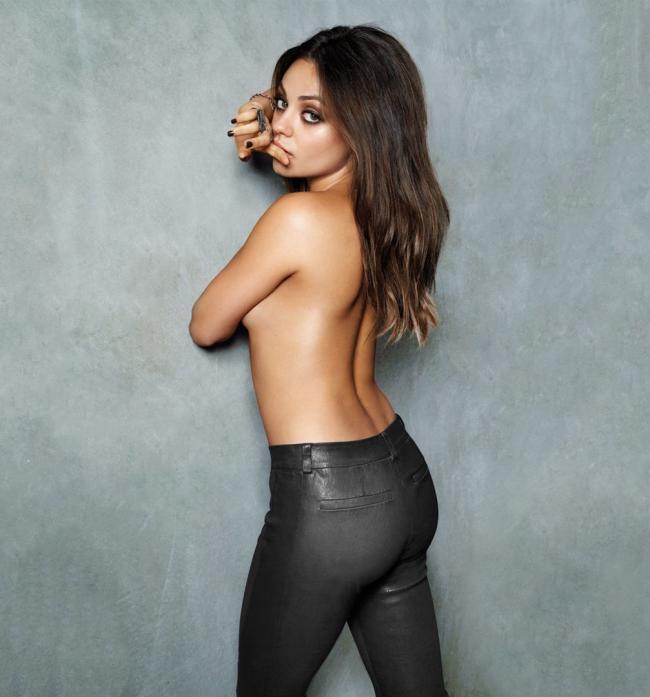 Мила Кунис фото стоит в черных обтягивающих штанах, вполоборота к стене, оголенный торс