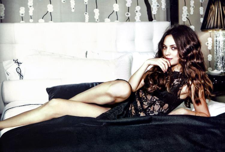 Мила Кунис в черном полупрозрачном платье, полулежит, сексуально сложила ноги