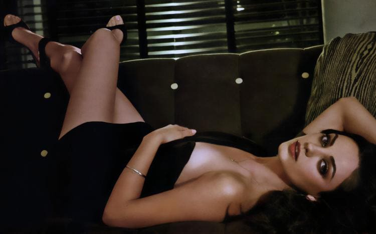 Мила Кунис обнаженная слегка прикрывшись покрывалом лежит на диване подняв ноги, яркий макияж