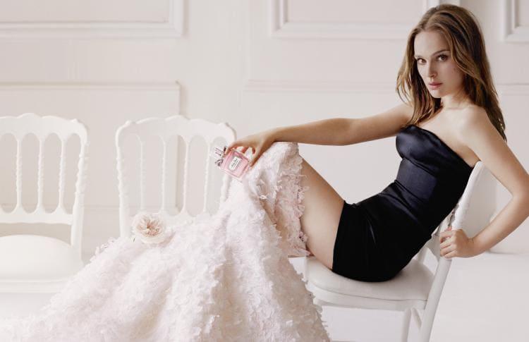 В черном очень коротком платье, сидит, подмышки оголены