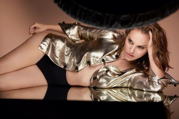 Лежит на боку в распахнутой золотистой кофте черные трусики шортами