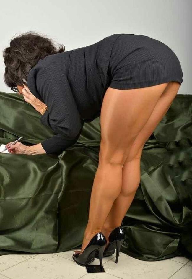 Зрелая брюнетка в короткой юбке, блестящих колготах стоит раком у дивана, туфли на высоком каблуке