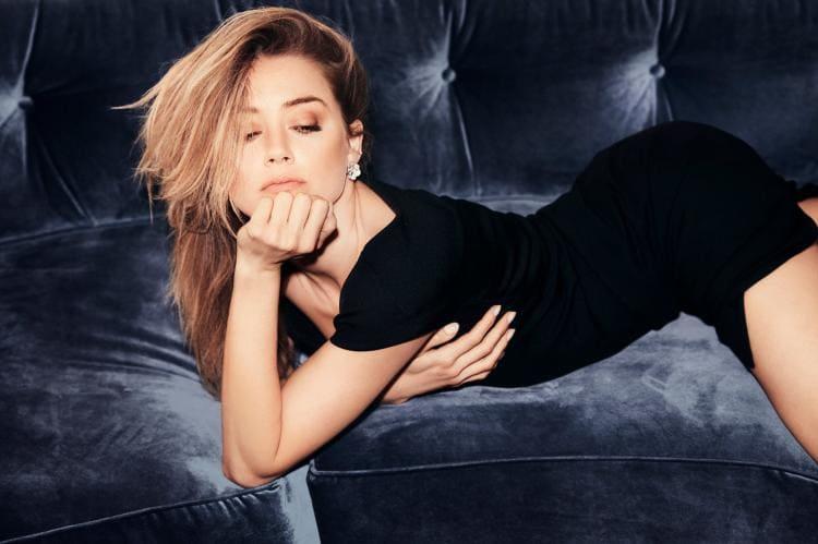 На диване на животе лежит в черном коротком платье