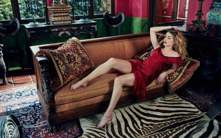 Лежит на диване в красном платье, оголив прекрасные ножки и ступни