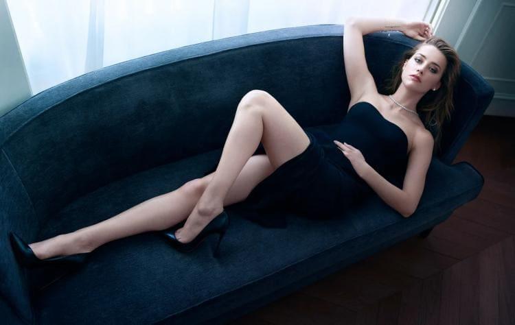 Лежит на диване в черном платье оголив ноги