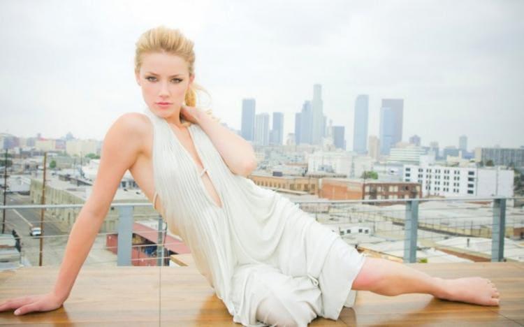 В белом воздушном платье на голое тело полулежит на крыше